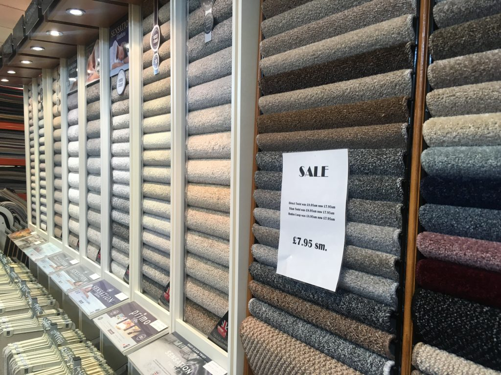 Allander Flooring picture of a rack of different colours and styles of carpets.