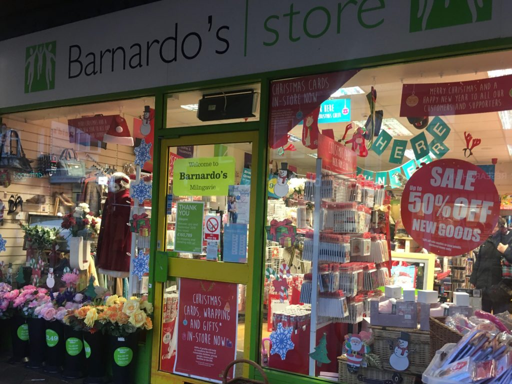 Barnardo's shop displaying 50% off sale and Christmas goods in window.